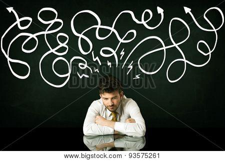 Depressed businessman sitting under white drawn direction lines