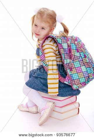 little girl  blonde  with a school knapsack on his back  sittin