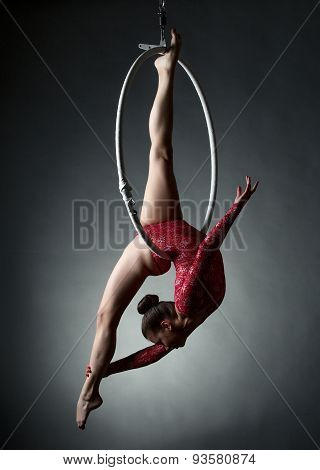 Studio photo of acrobatic girl dancing with hoop
