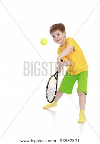 little boy with a tennis racket while hitting the ball