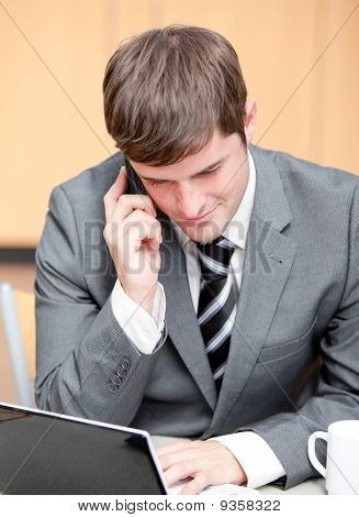 Concentrated Businessman Using His Laptop While Talking On Phone