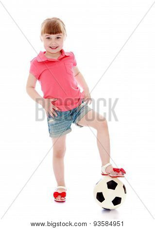 Cheerful little girl put her foot on a soccer ball