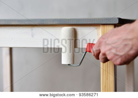 Man painting a wooden table using paint roller