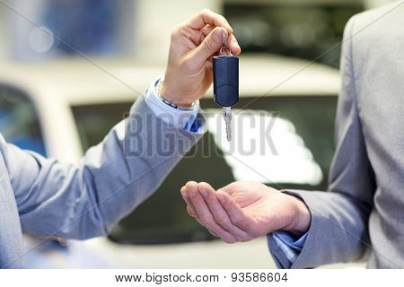 auto business, car sale, deal and people concept - close up of male hands with car key in auto show or salon