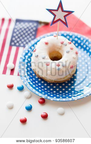 american independence day, celebration, patriotism and holidays concept - close up of glazed sweet donut with american flag and star decoration on disposable plate at 4th july party from top