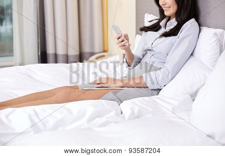 business trip, people and technology concept - smiling businesswoman with smartphone typing in bed at hotel