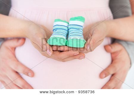 Close-up Of A Pregnant Woman Holding Baby Shoes And Of Her Husband