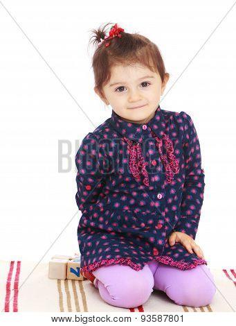 Little girl sitting on the rug in Montessori kindergarten