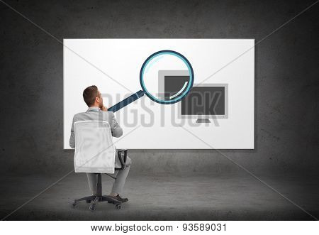 business, people and advertisement concept - businessman in suit sitting in office chair looking at computer and magnifier icons on screen on gray wall background from back