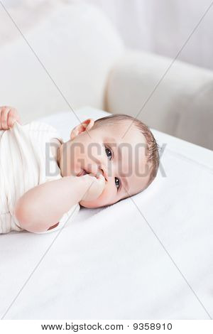 Portrait Of A Cute Baby Lying On Table In The Living-room