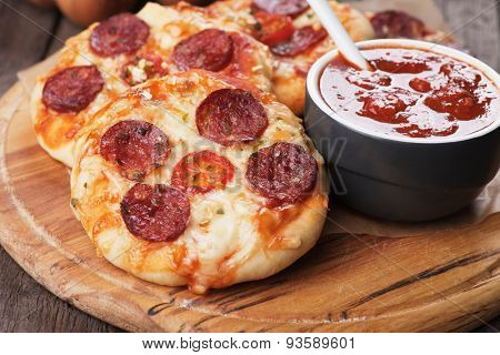 Mini pizzas with salami, cheese and tomato