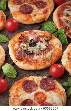 Mini pizzas with ham, salami, cheese and tomato
