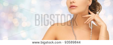 fashion, style, jewelry, beauty and people concept - beautiful woman wearing pearl earrings and necklace over blue holidays lights background