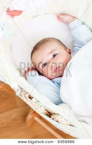 Portrait Of A Bright Baby Lying In His Cradle