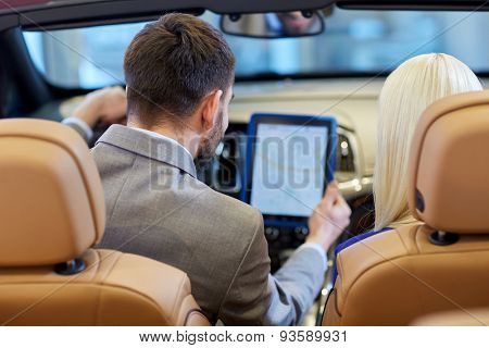 auto business, car sale, navigation and people concept - close up of couple sitting in cabriolet car with tablet pc computer at auto show or salon from back