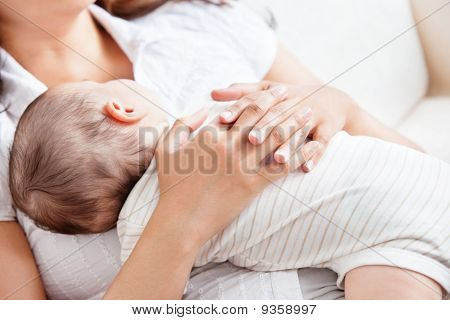 Delighted Young Mother Taking Care Of Her Adorable Baby