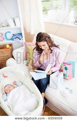 Bright Woman Sitting On The Sofa With Bags Reading A Card While Her Baby Is Sleeping In His Cradle