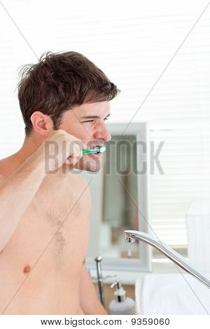 Good-looking Young Man Brushing His Teeth In The Bathroom