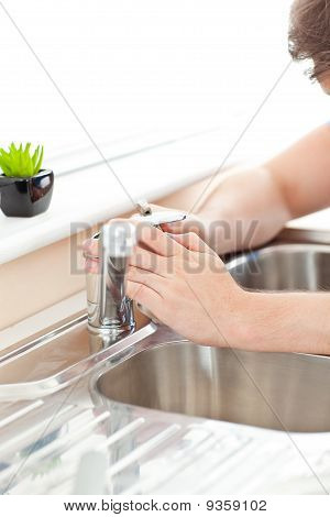 Close-up Of A Young Man Repairing His Sink In The Kitchen