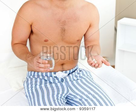 Depressed Young Man Sitting On His Bed And Holding A Glass Of Water And Pills In His Bedroom