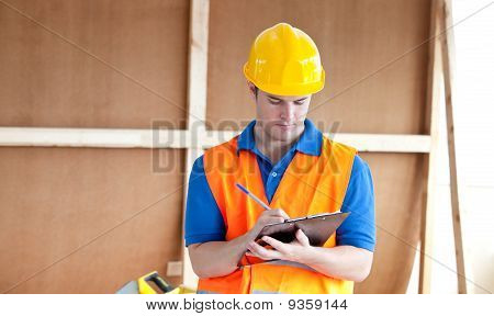 Self-assured Male Worker Writing On A Clipboard