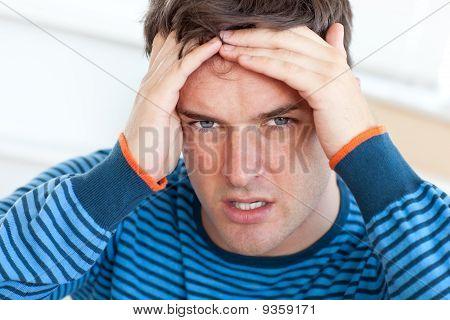 Caucasian Mann mit Kopfschmerzen In das Wohnzimmer