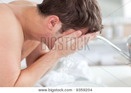 Cute Caucasian Man Spraying Water On His Face After Shaving In The Bathroom