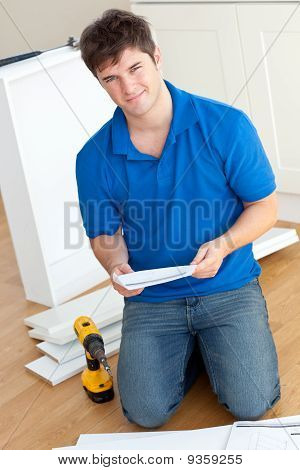 Charismatic Young Man Reading The Instructions To Assemble Furniture In The Kitchen
