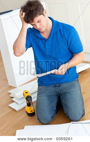 Incomprehensive Young Man Reading The Instructions To Assemble Furniture In The Kitchen