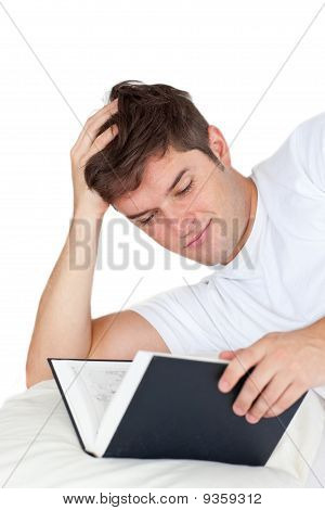 Attractive Man Reading A Book Lying On His Bed