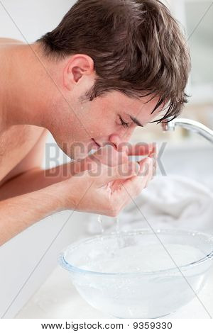 Positive Caucasian Man Spraying Water On His Face After Shaving In The Bathroom