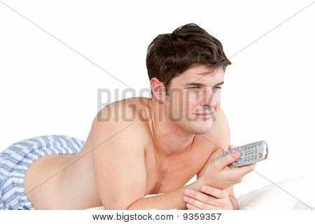 Handsome Man Holding A Remote Lying On His Bed