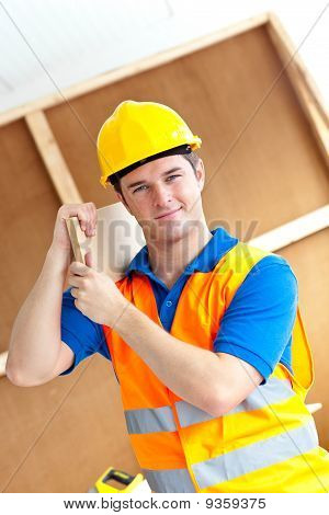 Self-assured Young Male Worker With A Yellow Helmet Carrying A Wooden Board