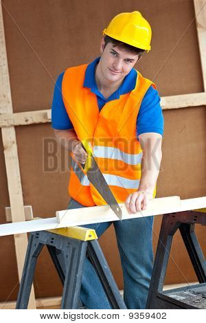 Charismatic Male Worker Wearing A Yellow Hardhat Sawing A Wooden Board