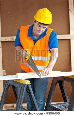 Handsome Male Worker Wearing A Yellow Hardhat Sawing A Wooden Board