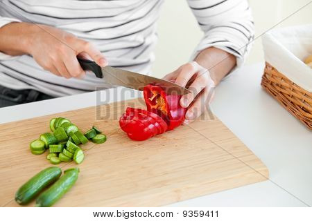 Close-up Of A Young Man Cutting Vegetables In The Kitchen