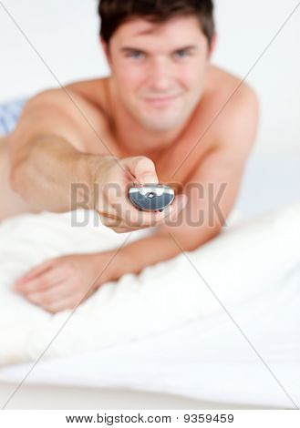 Good-looking Man Holding A Remote Lying On His Bed