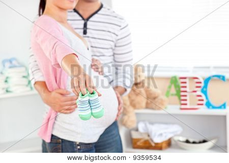Close-up Of A Bright Pregnant Woman Holding Baby Shoes While Husband Touching Her Belly In The Room