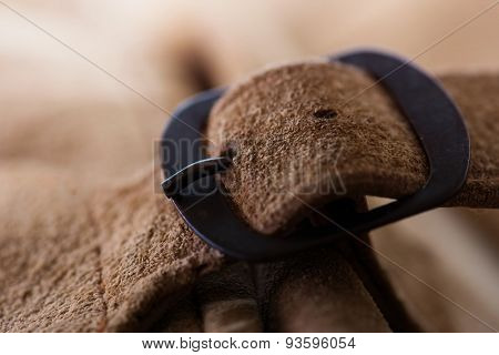 Fastened buckle. Buckle section of a leather bag or case. Extremely shallow depth of focus. Focus is on buckle pin. suede leather.