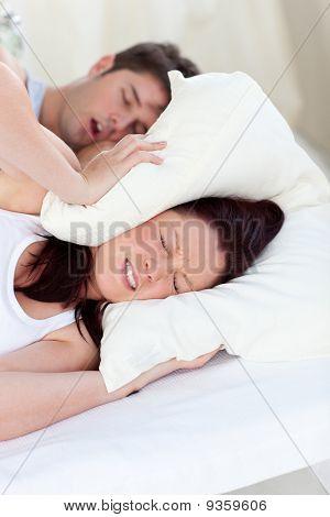 Junge Frau gestört durch die Schnarcher von ihrem Freund im Schlafzimmer