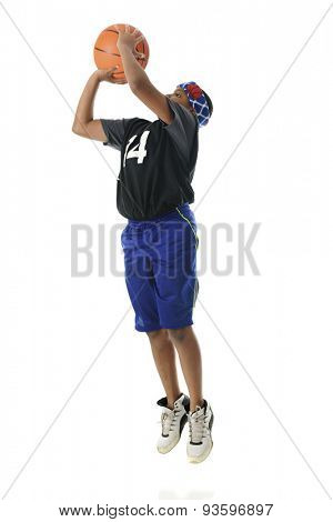 A preteen athlete making a basketball jump shot.  Includes motion blur.  On a white background.