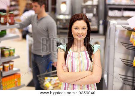 Retrato de un minorista de alimentos sonriente con un cliente masculino en su tienda de diario