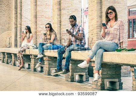 Group Of Young Multiracial Friends Using Smartphone With Mutual Disinterest Towards Each Other