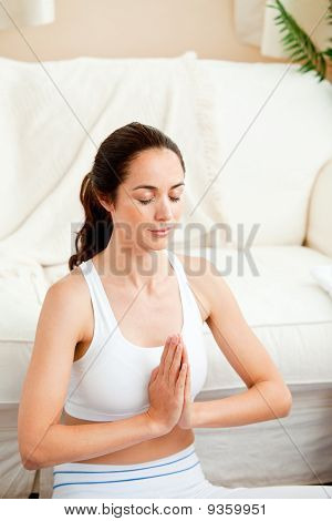 Concentrated Hispanic Woman Meditating In Her Living-room