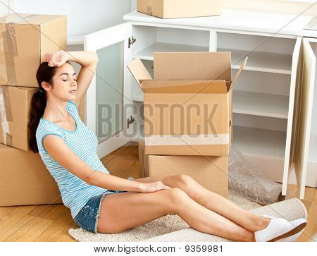 Tired Hispanic Young Woman Sitting On The Floor After Unpacking Boxes