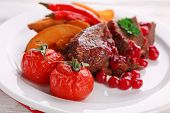 stock photo of deer meat  - Tasty roasted meat with cranberry sauce and roasted vegetables on plate - JPG