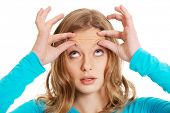 image of forehead  - Teenage woman checking wrinkles on forehead  - JPG