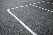 picture of parking lot  - Empty slots on urban parking lot white marking lines over gray asphalt pavement - JPG