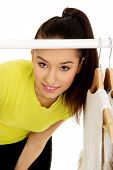 pic of clothes hanger  - Young beautiful woman with clothes on hanger - JPG
