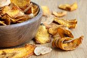 stock photo of parsnips  - Detail of fried carrot and parsnip chips in rustic wood bowl - JPG